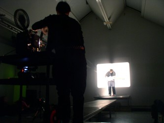Emma Hart in foreground with projector, Ben Drew in distance with guitar