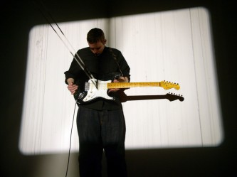 Ben Drew holding a guitar with film loop, projection of film over him