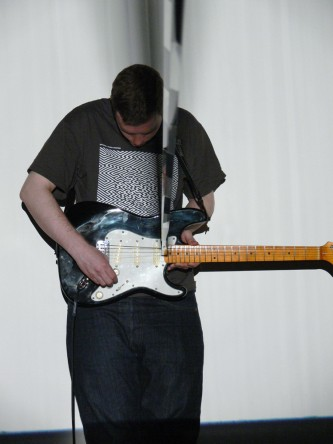 A man standing holding an electric guitar, a band of film looped in the strings