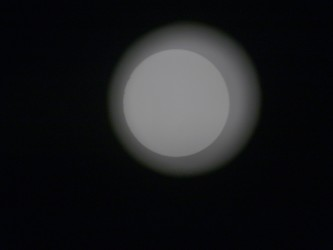 A circle of light on a projection screen with a pale halo around it