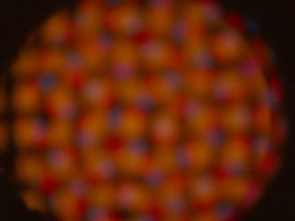 Blurry orange circle of blurry dots of purple orange and red on a screen