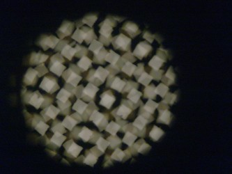 A pattern of pale, faceted shapes on a projection screen