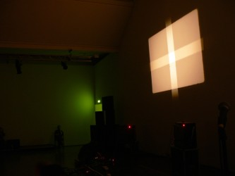 A large cross projected onto a screen, a green light in the room to the left