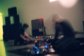 Blurred electronics, flora like on the floor. Two musicians in front of a screen