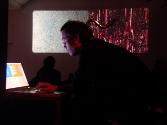 Man with bass clarinet operating a computer in front of a screen with projection