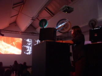 Jennifer Reeves operating a projector, images cast on far away wall