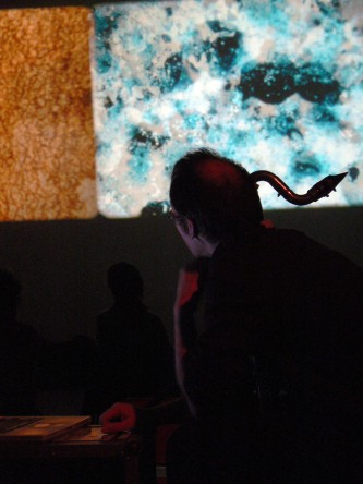 Bass clarinet player Anthony Burr in front of a screen showing abstract images