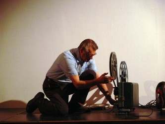 A man setting up a projector on a floor