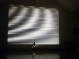 Horizontal bands of light on a screen, a projector in front of it