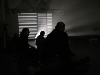 People seated on the floor by a screen showing horizontal bands of light