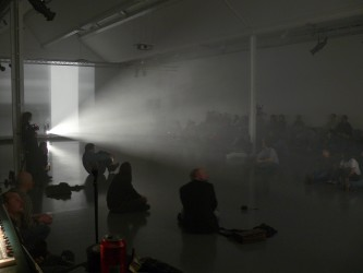 A large room with projectors and a haze of light, many people sitting around