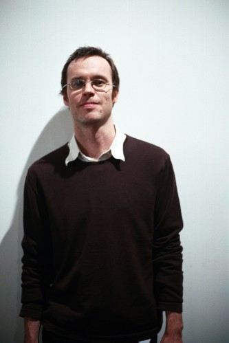 Portrait of Anthony Burr in a black jumper against a white background