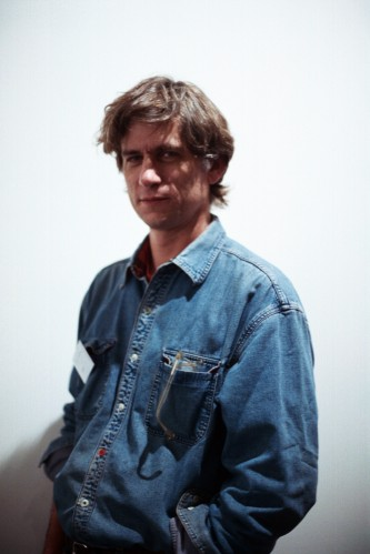 Portrait of Bruce McClure standing in a blue shirt, hands in shirt pouch