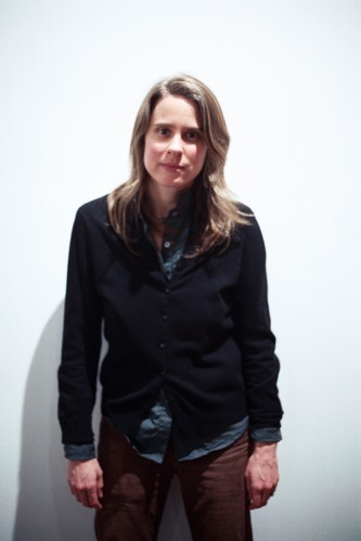Portrait of Jennifer Reeves against a white background, arms dangling