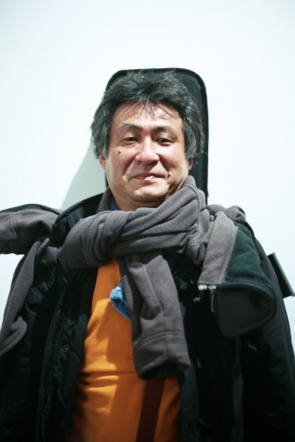 Kazuo Imai portrait with orange jumper, scarf and guitar backpack