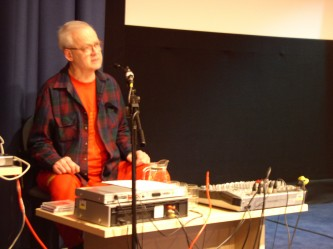 Tony Conrad seated behind a table with mixer and cables. His t shirt is orange