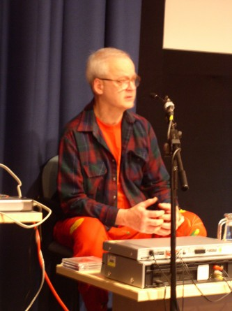 Tony Conrad seated in orange tropical fruit patterned trousers