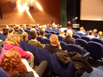 A cinema full of people, in the distance Tony Conrad moves some papers