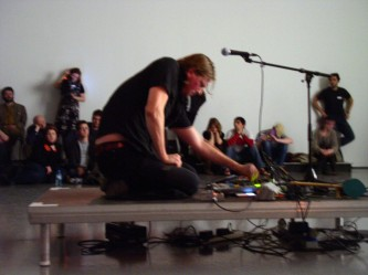 Daniel Menche on a little platform adjusting a mixer surrounded by audience