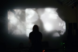 Daniel Menche silhouetted against a screen showing abstract textures