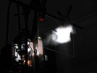 Close up of a projector and a slide with light passing through it