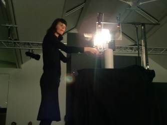 Sandra Gibson adjusting a slide in front of a projector