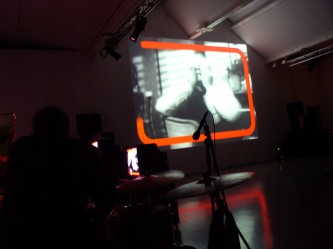 A woman's face and hands framed by orange lines on a screen, musicians nearby