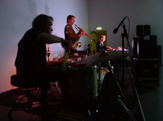 Paul Lovens drumming John Butcher with sax Steve Beresford in the distance