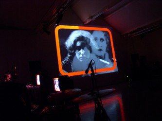 Two women's faces on a screen with orange frame added, reflections on the floor