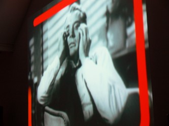 A clip from a film, of a woman projected on a screen with red lines added