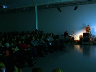 Audience and musicians in darkness, drums and saxophone on right side