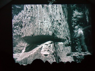 A black and white image of lumber jacking projected on a screen