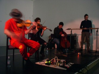 Tony conrad dressed in orange with a hat playing violin with 3 musicians