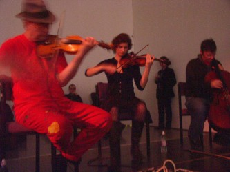 Tony, Angharad, Nikos playing violins and cello respectively TC in orange