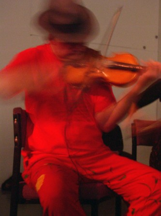 A man wearing orange clothes and a brown hat plays a violin