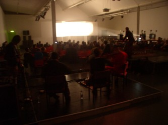 A screen lit white from projectors in a large room full of people