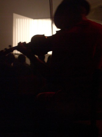 Tony Conrad's silhouette with violin against projection of his film