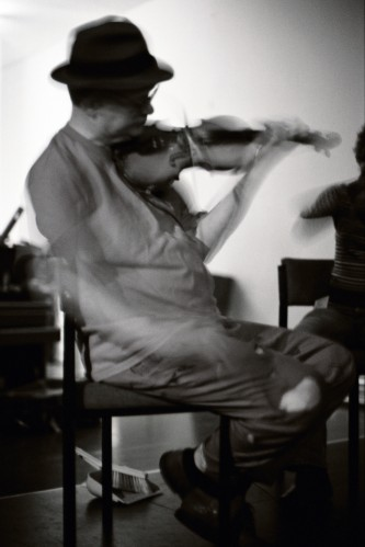 Tony Conrad in a hat playing a violin in Dundee