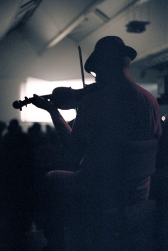 Purple aura Tony Conrad with violin silhouetted against projection screen