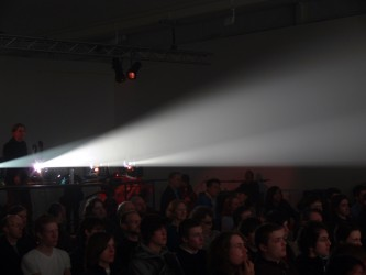 The glare of four projectors above a seated audience