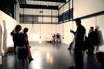 A white room with people milling around, lightbulbs suspended in the middle