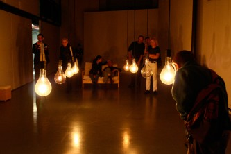 A dimly lit room populated with people, lightbulbs suspended in the middle