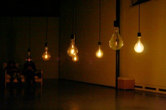 A series of large dimly lit light bulbs hanging in a room, fewer lit