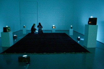 A room full of radios with fluorescent tube lights, a red rug on the floor