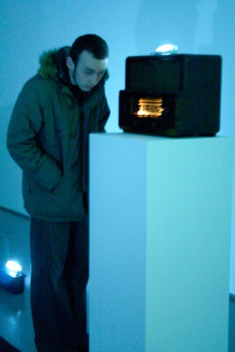 A man inspects a radio on top of a plinth in blue light