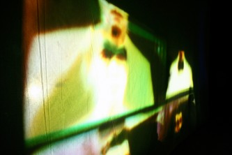 Green and yellow forms projected onto a sheet from within