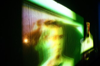 A distorted projection of a face and other images showing on a screen