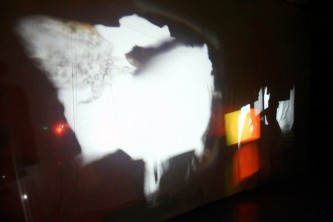 A large cube constructed from fabric showing projections cast from the inside