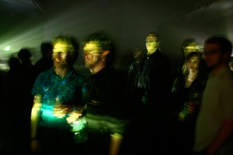 Smiling faces in fragmented beams of light, an audience