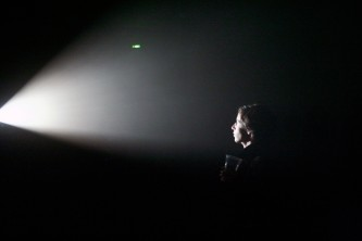 An audience member staring into the light of Greg Pope's Light Trap